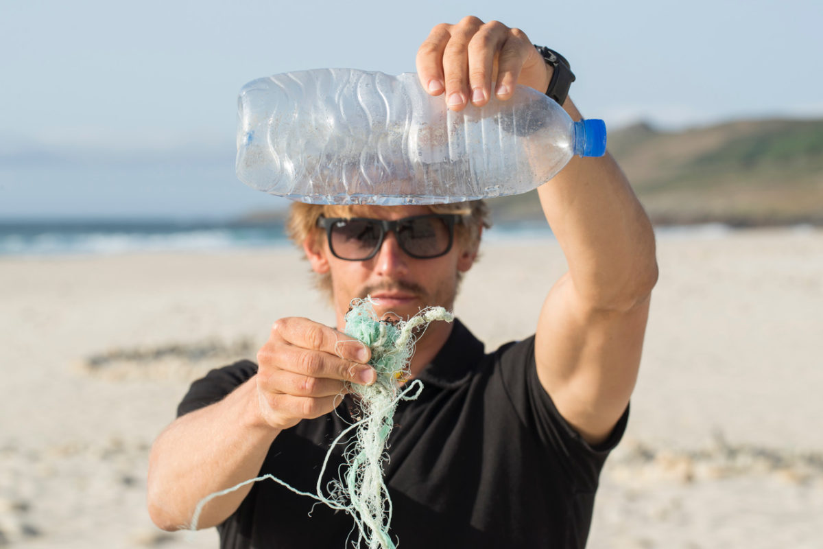 Florian Jung holding up trash on the beach